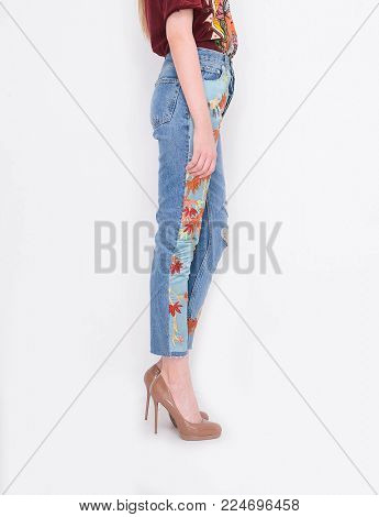 Side view Fashion. Woman legs in embroidered flowers, jeans and high heels shoes posing