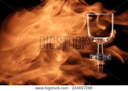 An empty glass of port or sherry isolated on a black background in the fire flames.