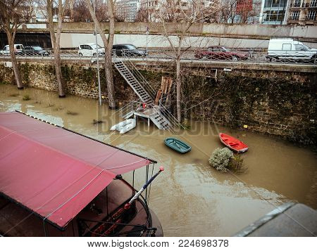 PARIS, FRANCE - JAN 30, 2018: Swollen river Seine river's embankments overflow after days of heavy rain - boas used for people living on the Peniche barges