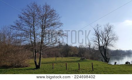 River picnic area with cut green grass, wooden table with benches, barbeque area and tall trees without leaves surrounded with smaller vegetation in late autumn