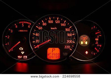Car dashboard glowing in dark.