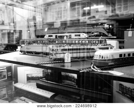 PARIS, FRANCE - JAN 30, 2018: Store window facade selling multiple toy collectible model trains featuring all railways in the world in central Paris, France black and white