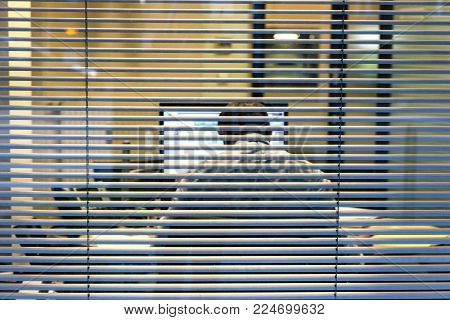 Silhouette of working late businessman man seen through windows blinds working report thesis data analysis bank report view from treet - working late concept at business