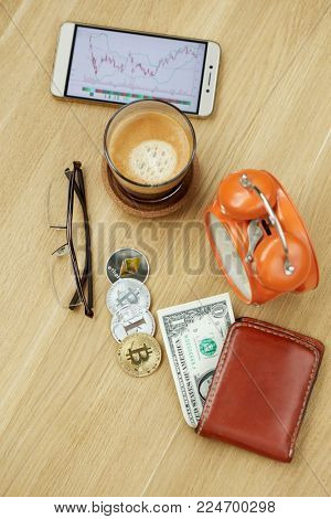 Smartphone with financial charts, glass of coffee, glasses, red wallet with banknotes, crypto-coins, alarm-clock on wooden desk, top view.