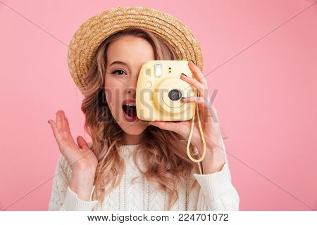 Photo of pretty young woman standing isolated over pink background. Looking camera holding camera.