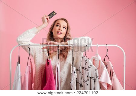 Photo of amazing beautiful lady choosing clothes hanging on rack in workshop holding debit card.