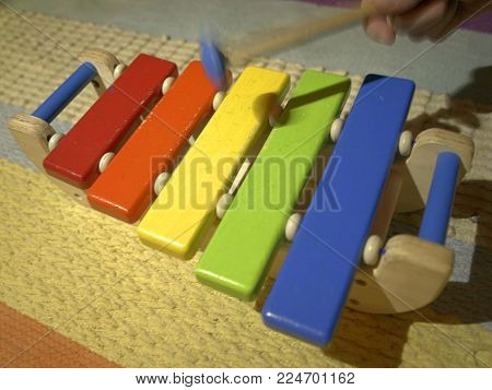 Colorful wooden toy xylophone beeing hit, with motion blur at the mallet.