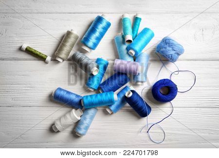 Sewing threads with clews on wooden background, top view