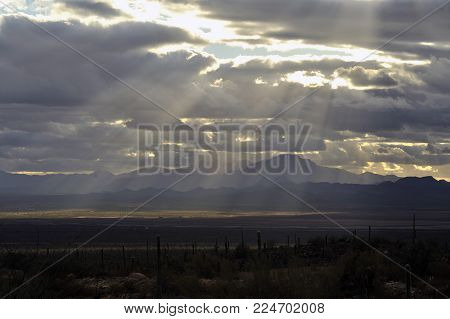 Silver Lining Sun Rays through the clouds with Saguaro Cactus, Desert and Mountains in the background.