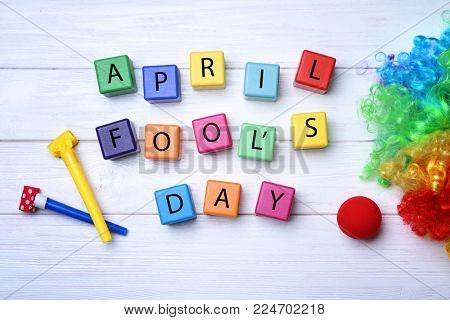 Party horns, cubes and rainbow wig on wooden background. April fool's day celebration