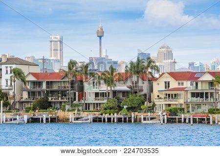 AUSTRALIA, SYDNEY - MARCH 21, 2014: Sydney Harbour water front houses wih city skyline behind
