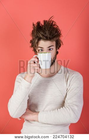 Insomnia, refreshment and energy. Cold and flu, single. Surprised guy with tea cup on red background. Morning with coffee or milk. Man with disheveled hair drink mulled wine.
