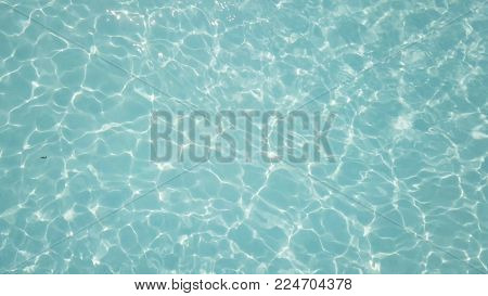 Water in swimming pool rippled water detail background. Water in swimming pool with sun reflection. Blue swimming pool rippled water detail.