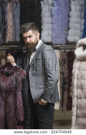 Man With Beard And Mustache Hold Fur Coat. Guy At Furry Coat In Shop With Fur On Background. Luxury