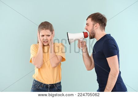 Young man shouting into megaphone at woman on color background. Problems in relationship