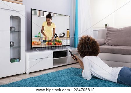 Woman Lying On Carpet Watching Television At Home