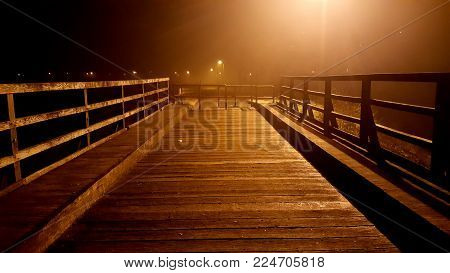Wooden bridge access blocked with massive metal handrails at foggy night with bright city lights and uncut grass in background