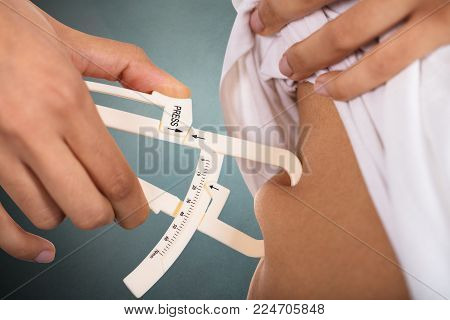 Close-up Of A Woman's Hand Checking Stomach Fat With Caliper