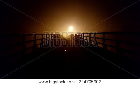 Old massive wooden bridge with wooden handrails at night surrounded with thick fog and bright city lights in background