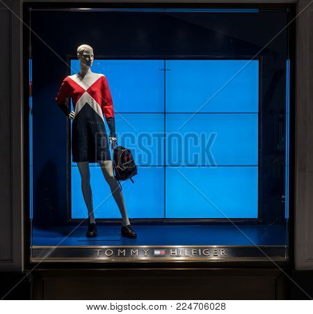 Tommy Hilfiger at Emquatier, Bangkok, Thailand, Jan 6, 2018 : Luxury and fashionable brand window display. Isolated mannequin with casual dress holding mini bag against TV monitor at flagship store.