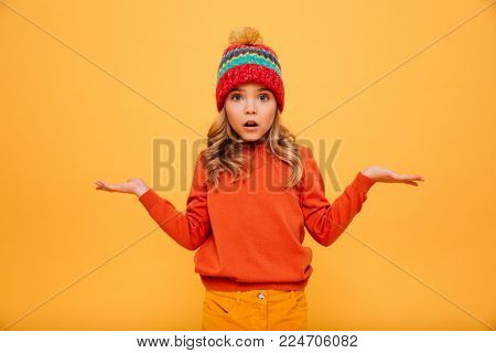 Surprised Young girl in sweater and hat shrugs her shoulders while looking at the camera over orange background