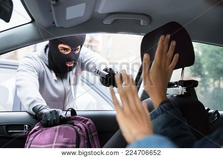 Thief In Balaclava Threatening Woman With Gun While Stealing Backpack From Car