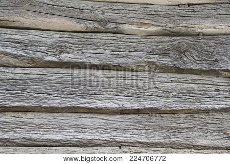 old wooden background of several rotten oak logs with twigs, front view