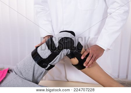 Physiotherapist's Hand Examining Patient's Knee With Knee Braces