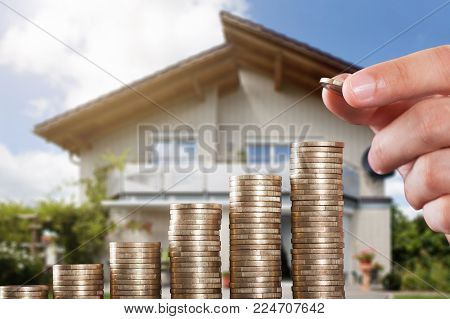 Human Hand Placing A Coin On Increasing Coin Stacks In Front Of House