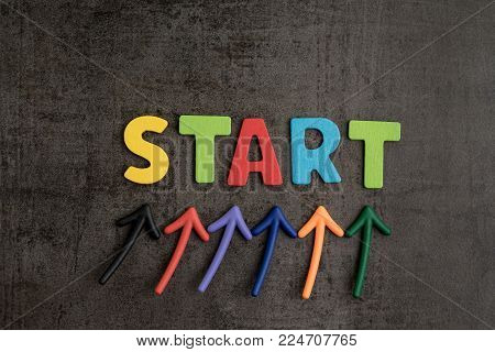 Business start begin the journey concept, colorful arrows point up to word START on blackboard cement wall to emphasize the important of initiation  thinking, brave and think out of the box.