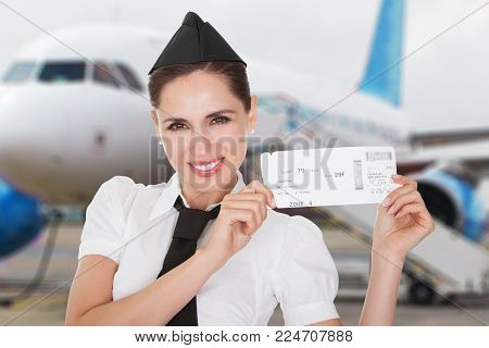 Portrait Of A Smiling Young Stewardess In Front Of Airplane