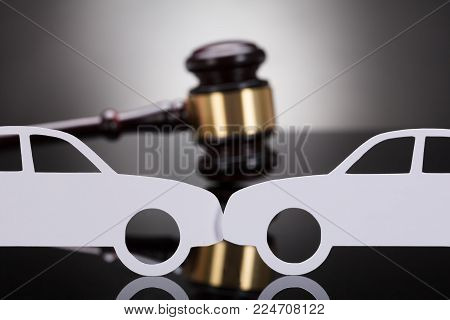 Close-up Of Paper Cars In Front Of Gavel On Grey Background