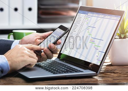 Close-up Of A Businessperson's Hand Working With Gantt Chart On Mobile Phone
