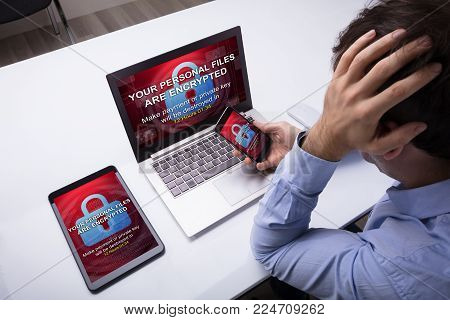 Worried Businessman With Cellphone, Digital Tablet And Laptop With Encrypted Text On The Screen