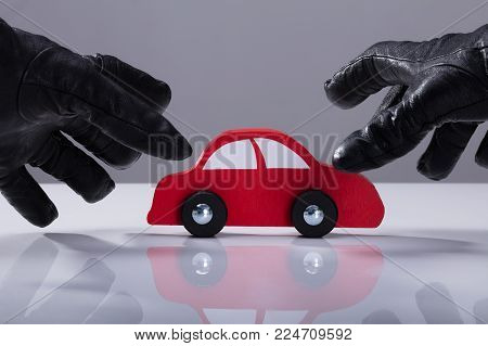 Close-up Of A Thief's Hand Wearing Gloves Stealing Red Car