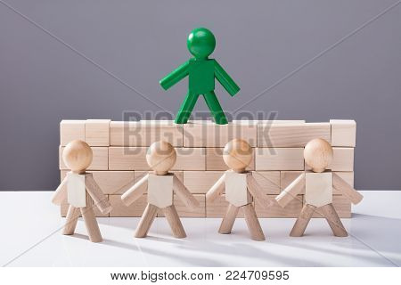Row Of Figures In Front Of Figure Standing On Top Of Wooden Blocks