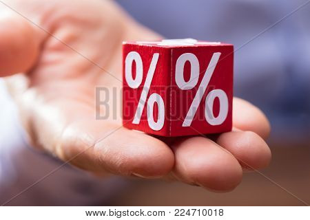 Close-up Of Hand Holding Red Wooden Block With White Percentage Symbol On It