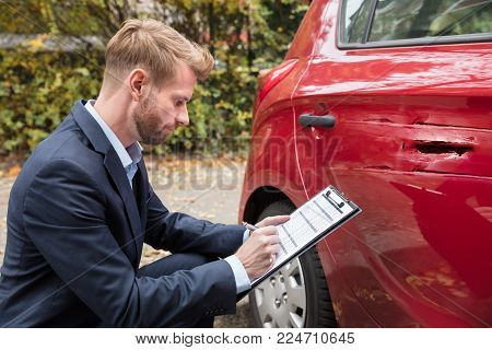 Insurance Agent Writing On Clipboard While Examining Car After Accident