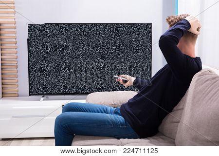 Man Sitting On Sofa Looking At Television With No Signal