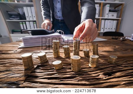 Businessperson Calculating Stacked Golden Coins With Calculator On Wooden Desk