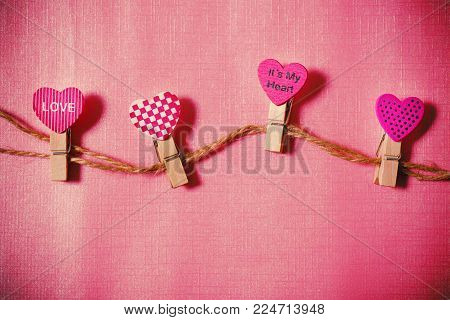 Decoration heart shape clothes pegs on pink background, Valentine concept