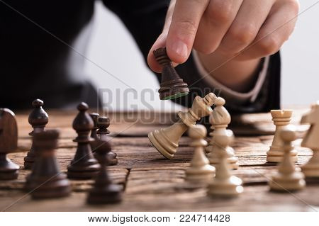 Close-up Of A Businessperson Checkmating King Chess Piece With Rook On Wooden Desk