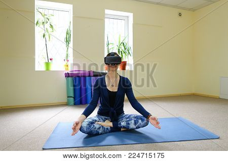 Lady works mutters by phone at yoga. Busy girl doing sports in light spacious gym. Concept of multitasking, telecommuting.