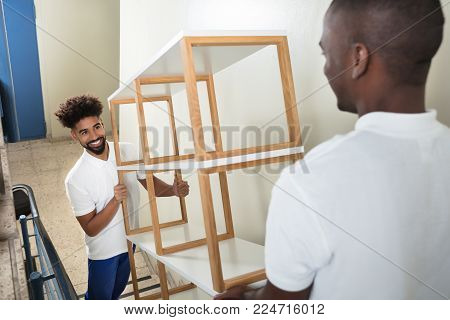 Two Male Movers Carrying The Empty White Shelf On The Staircase At Home