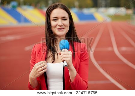 Young smiling woman journalist speaks into microphone at stadium.