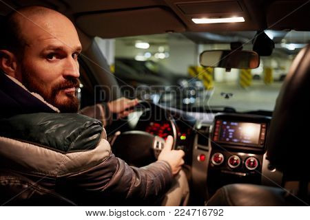 Bearded man sits half-turned on driver seat in car at underground parking.