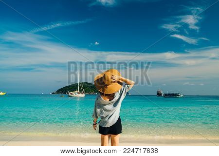 Rear view of young woman traveler with hat relaxing on the beach at similan islands in Andaman sea at Phang Nga province near Phuket and Krabi in southern of Thailand. Summer Relax
