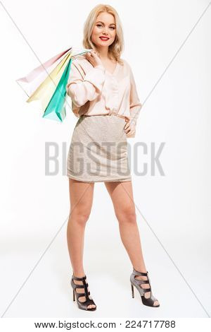 Photo of a beautiful young woman standing isolated over white background holding shopping bags looking camera.