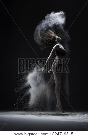 Graceful girl in top and shorts jumping in a cloud of white dust full-length shot in dark room