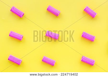 Pink curlers for hairdress. Pattern on yellow pastel background top view.